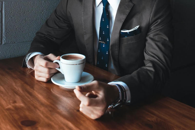 A young man is sitting at a table in a suit taking a coffee break.