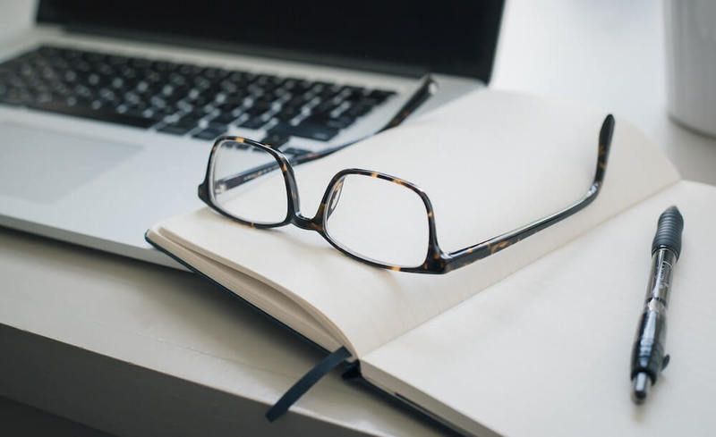 A photo of a laptop on a desk with a pair of reading glasses, a notebook, and a pen.